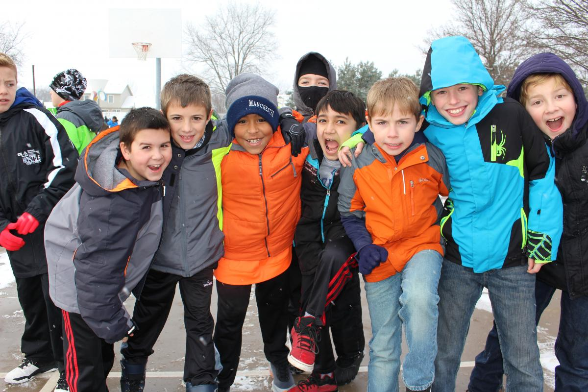 Laughing children on the school playground in winter coats
