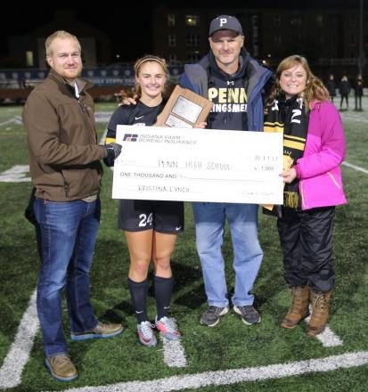 An IHSAA representative presents the IHSAA Mental Attitude Award to Penn's Kristina Lynch and her parents